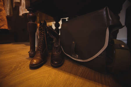 antique shop: Close-up of antique shoes and bag on wooden floor in antique shop