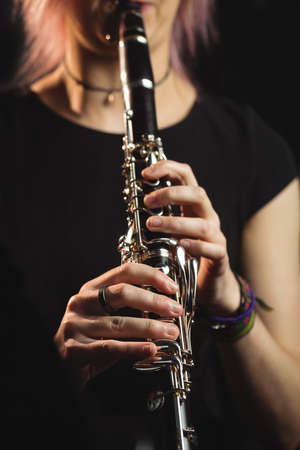 Mid-section of woman playing a clarinet in music school LANG_EVOIMAGES
