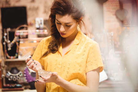antique shop: Woman looking at glass candle stand in antique shop