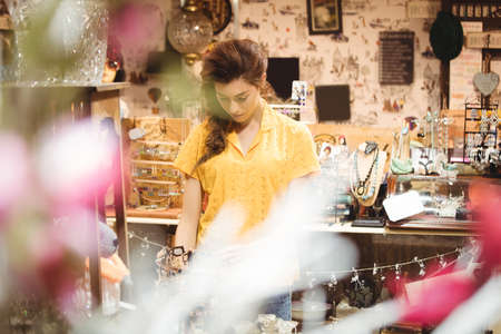 antique shop: Woman looking at vintage jewellery in antique shop LANG_EVOIMAGES