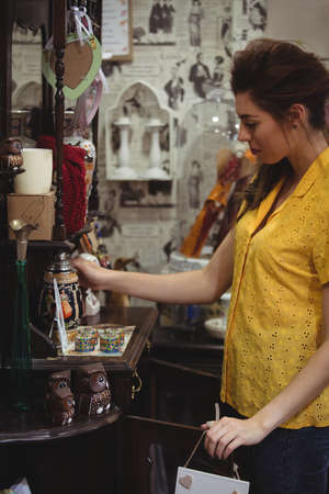 antique shop: Woman looking at vintage jar in antique shop
