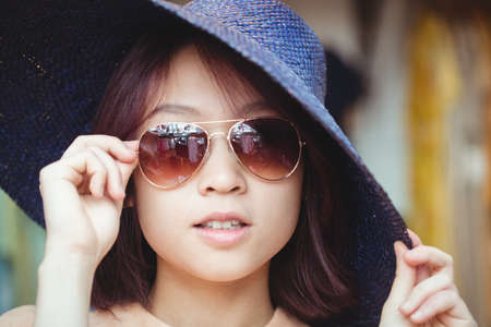 people: Woman wearing sunglasses in boutique shop LANG_EVOIMAGES