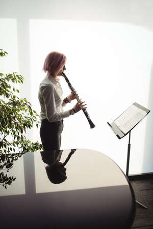 clarinete: Attentive woman playing a clarinet in music school