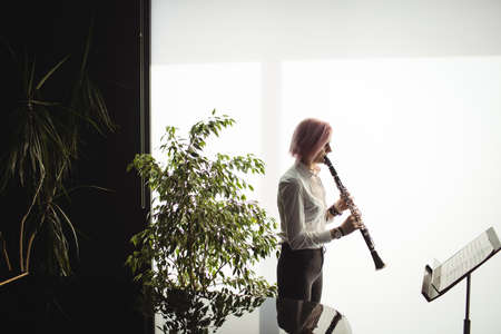 attentive: Attentive woman playing a clarinet in music school