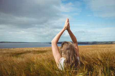Woman with hands raised over head in prayer position in field on a sunny day