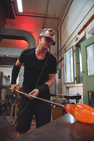 molten: Glassblower shaping a molten glass on marver table at glassblowing factory