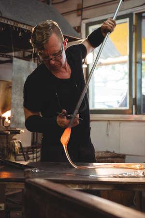 glassblower: Glassblower working on a molten glass at glassblowing factory