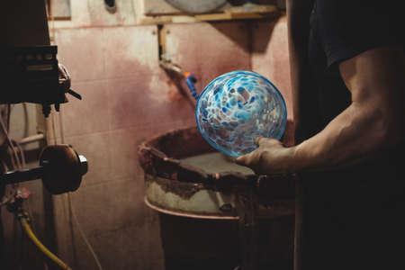 glassblower: Glassblower holding a glassware at glassblowing factory