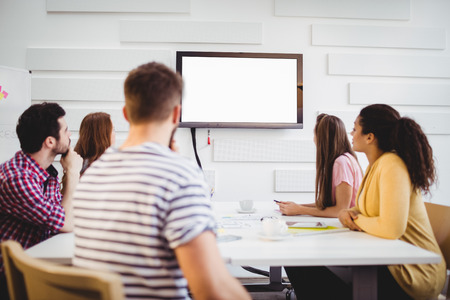 Young executives watching at television during training in creative office