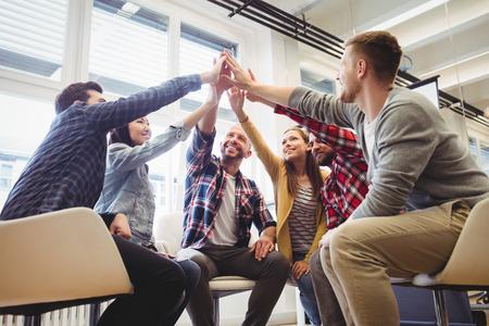 Faible angle de vue des gens d'affaires créatifs heureux donnant cinq haut dans la salle de réunion au bureau créatif