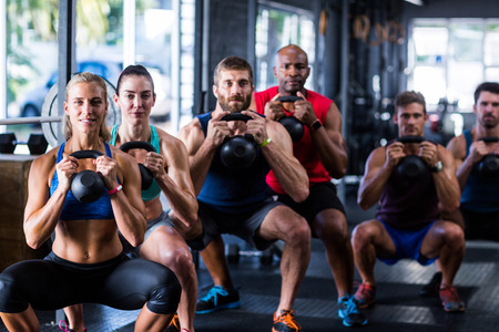Portrait of people holding kettlebells while crouching in gym Stock Photo