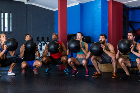 crouching: Friends holding exercise ball while crouching in gym
