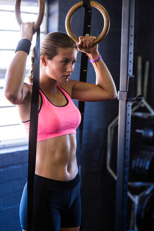 Woman holding gymnastic rings while exercising in gym