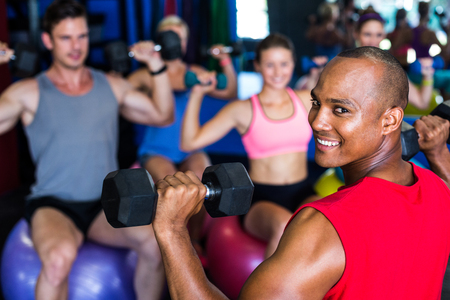 Portrait of smiling man holding dumbbell while exercising in gym