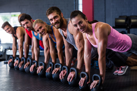 Portrait of smiling friends doing push-ups with kettlebell while exercising in gym