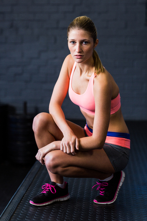 crouching: Portrait of fit serious woman crouching in gym Stock Photo