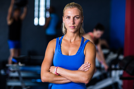 Portrait of serious woman with arms crossed  while standing in gym
