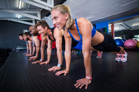 Smiling friends doing push-ups while exercising in gym Stock Photo