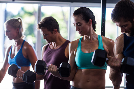 working out: Young friends holding dumbbells while working out in gym Stock Photo