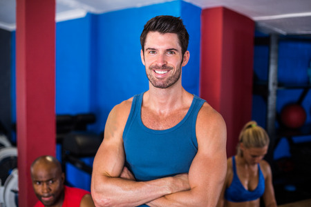 free weight: Portrait of smiling man with arms crossed while standing in gym Stock Photo
