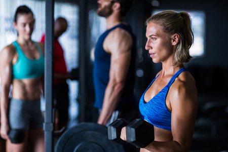 Thoughtful woman lifting dumbbell while standing in gym