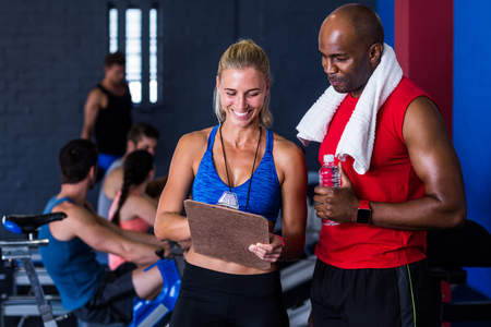 Smiling fitness instructor discussing with man standing in gym Stock Photo