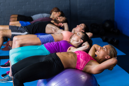 fitness ball: Male and female athletes exercising on fitness ball in gym Stock Photo