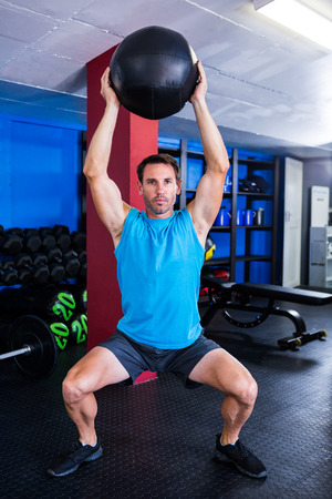 healthy men: Portrait of serious athlete holding exercise ball in gym