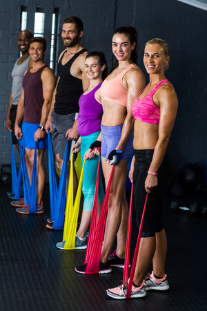 resistance: Portrait of male and female athletes exercising with resistance band in gym