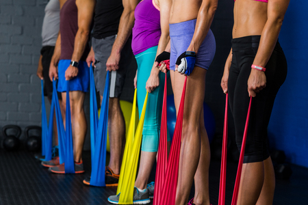 resistance: Athletes exercising with resistance band in gym