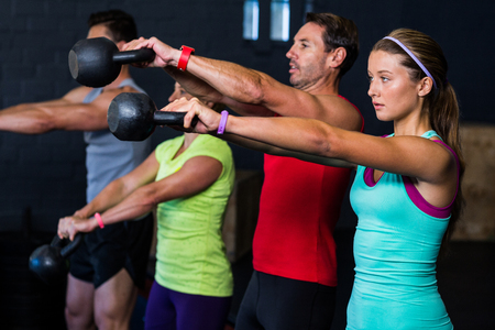 self care: Male and female athletes exercising with kettlebells in gym