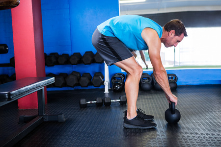 Side view of athlete with kettlebell while exercising in gym Stock Photo