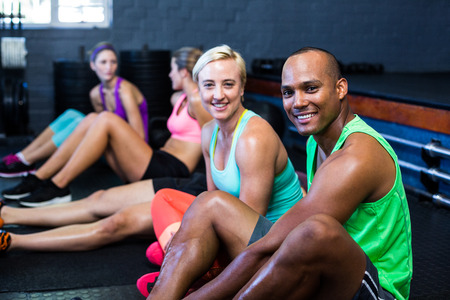 Portrait of smiling male and female athletes in fitness studio