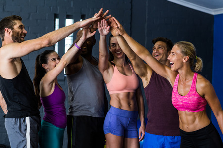 Cheerful male and female athletes stacking hands in fitness studio Stock Photo