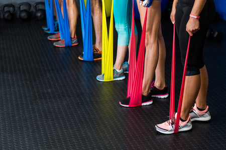 resistance: Low section of athletes exercising with resistance band in fitness studio