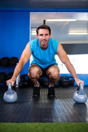 crouching: Portrait of smiling athlete with kettlebell while crouching in gym