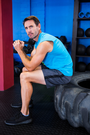Portrait of serious male athlete sitting on tire in gym Stock Photo