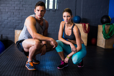 crouching: Portrait of confident male and female athletes crouching in fitness studio Stock Photo