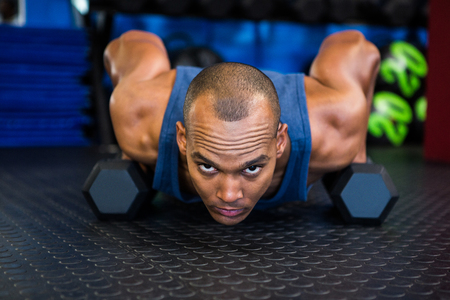 Portrait of serious man doing push-ups with dumbbell in gym