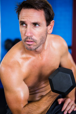 healthy men: Shirtless athlete holding dumbbell in gym