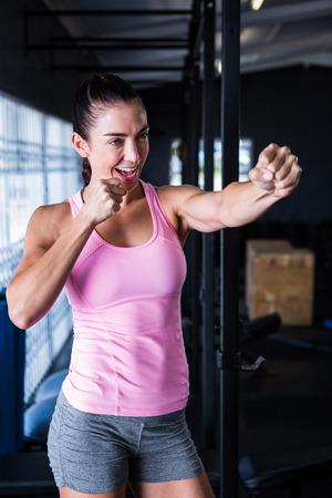 Smiling female athlete punching in gym