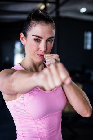 punched out: Portrait of confident female athlete punching in gym