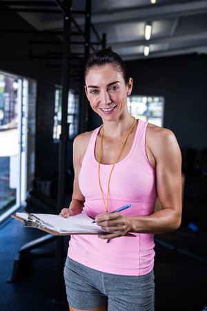adult  body writing: Portrait of happy fitness instructor holding clipboard in gym