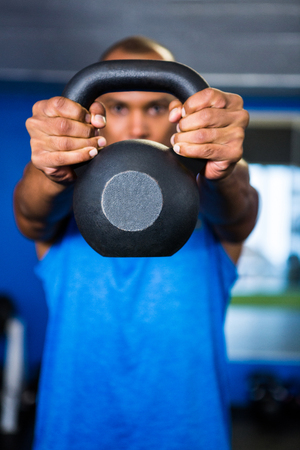 covering the face: Man covering face with kettlebell while exercising in gym