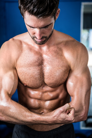 self care: Male athlete flexing muscles while standing in gym Stock Photo