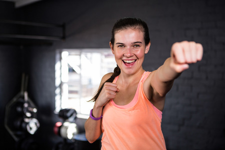 Portrait of smiling young woman punching while standing in gym