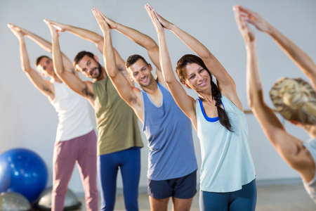 Instructor taking yoga class in fitness studio Stock Photo