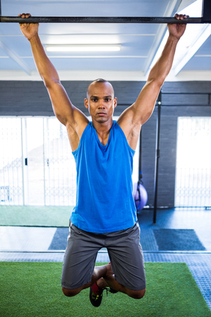 hairline: Portrait of male athlete doing chin-ups in gym