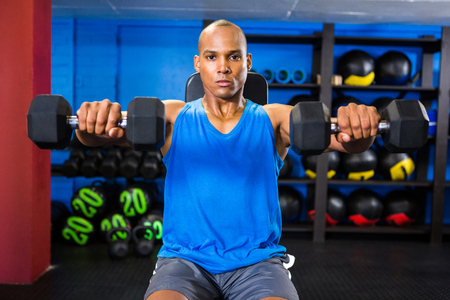 Portrait of male athlete exercising with dumbbells in fitness studio