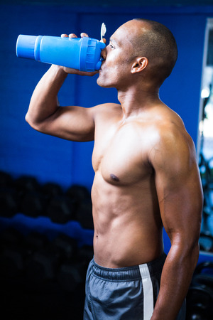 Side view of shirtless man drinking water in gym